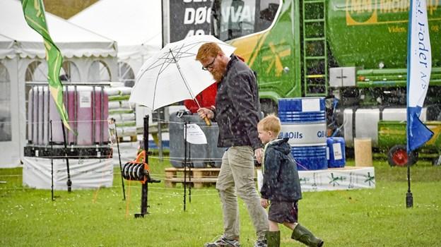 Far - selv om det regner, så skal vi altså lige over og kigge på traktorer..., synes denne dreng at sige, der trodser vejret, mens resten af de mange dyrskuegæster fik travlt med at komme ind i de mange telte. Foto: Ole Iversen Ole Iversen