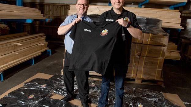 Niels Andersen, butikschef i Stark Dronninglund, og næstformand i Hjallerup Marked Stefan Jacobsen med dette års Hjallerup Marked trøje til de frivillige. Foto: Henrik Louis