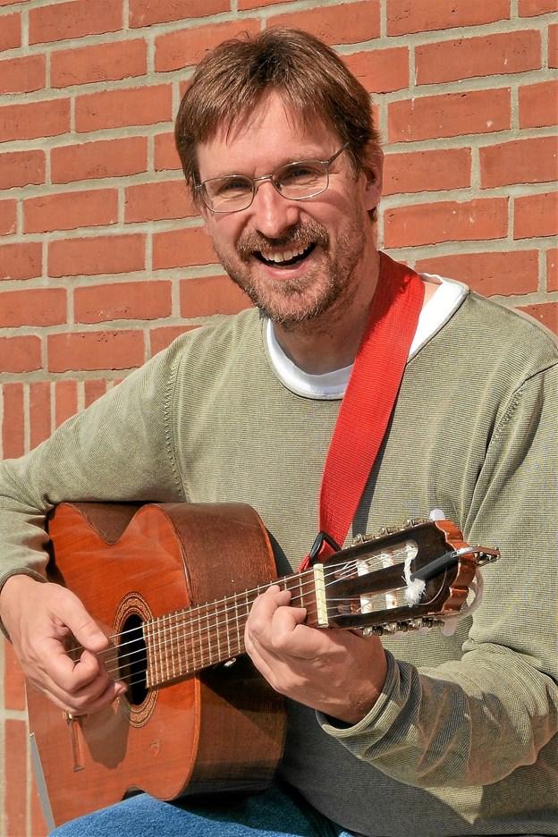 Organist og visesanger Asbjørn Høgholm, som den 6. november har skiftet orglet ud med en guitar til viseaften i Vindblæs   Foto: De 12 Kirker