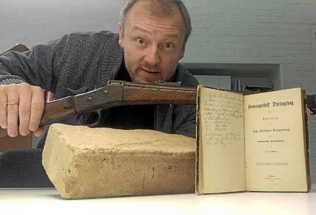 Hans Wendelboe viser et gammelt rustent gevær og en homøopatisk dyrlægebog, der på forunderlig vis blev udslagsgivende for oprettelsen af missionsstationen i 1918. Foto: Privatfoto Privatfoto