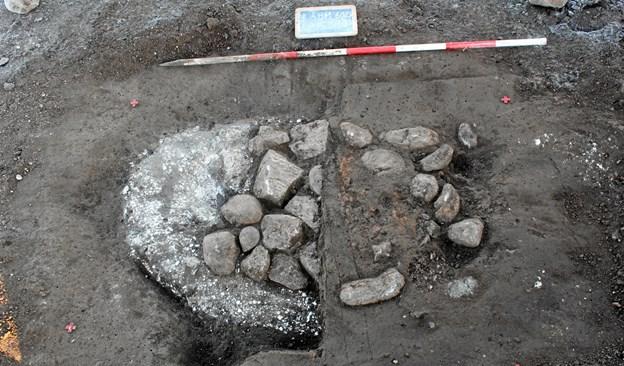 Her ses udgravningen af et ildsted. Det er opbygget på et underliggende kridtlag, hvorpå flere sten er lagt. Herover ses en rødbrændt lerkappe, der har dannet arnen. I forbindelse med udgravningen er den vestlige del af lerkappen bortgravet, og de underliggende sten er blevet fritlagt. Foto: Nordjyllands Historiske Museum