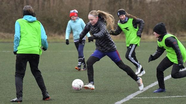 U14-pigerne træner hver tirsdag og torsdag. Da vi besøgte dem, viste vejret sig fra en af sine værste sider. Men det tog bestemt ikke modet fra de fodboldglade, som gik til den med liv og sjæl.