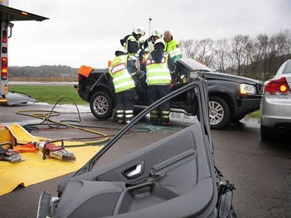 Svenske redningsfolk på kursus i at redde personer ud af en bil. Døre og tag er fjernet fra bilen, som næppe blir til bil igen.