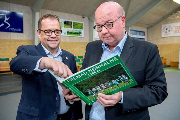 Claus Svendsen og DBU-formand Jesper Møller kigger i jubilæumsbogen, hvor Jesper Møller har skrevet forordet. Foto: Lars Pauli © Lars Pauli