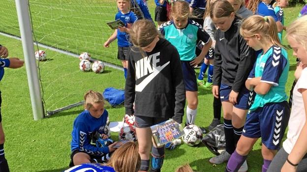 Matilde Kjeldgaard og Camilla Nielsen fra FC Thy, der ikke mindst var forbilleder for fodboldskolens piger, skriver her autografer på FIF's grønsvær. Foto: FIF