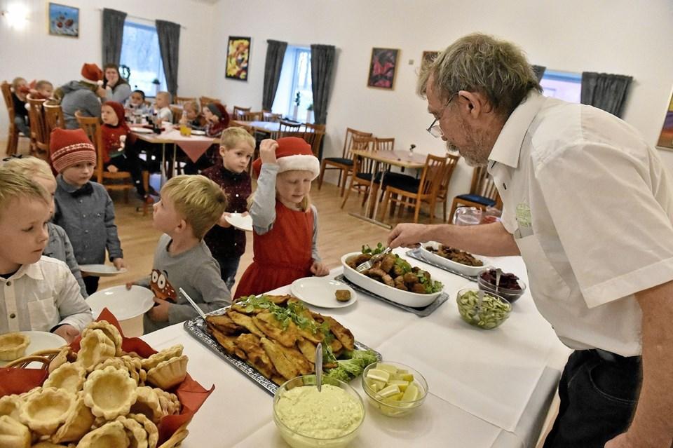 Krofatter Jørgen Jacobsen serverer frikadeller for Elisabeth med nissehue i den fine røde kjole. Foto: Ole Iversen Ole Iversen