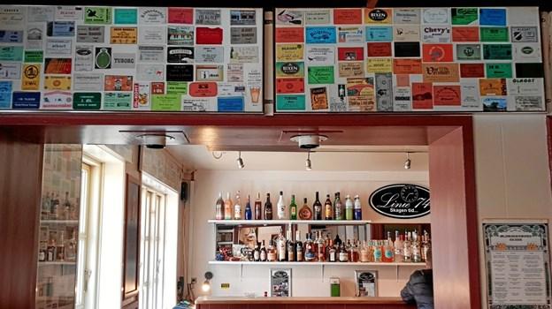 På væggene hænger der indrammede øl kuponer/visitkort fra forskellige værtshuse. Foto: Ole Svenden