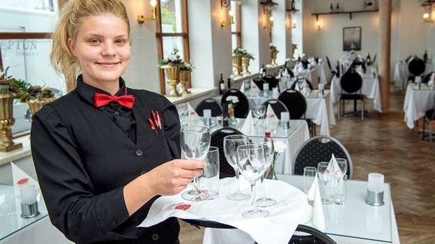 Der er mange opgaver, når man driver et hotel - Michelle Sørensen tager sig blandt andet af at gøre klar i restauranten.  Foto: Lars Pauli