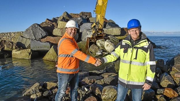 Havnedirektør Niels Clemensen (t.h.) trykker hånd med projektleder hos Per Aarsleff AS Mogens Steen Pedersen mens de sidste sten lægges i hullet i den nye 1060 meter lange mole i nord-øst. Foto: Ole Iversen