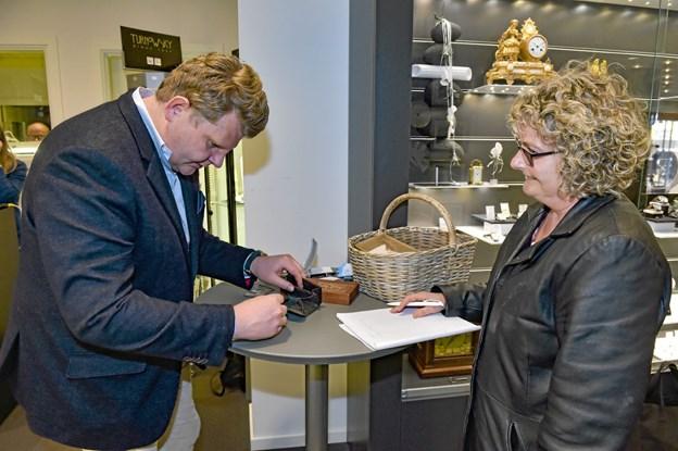 Bente Jeppesen Bisgaard havde sin fars gamle kro-pung med. Pungen, der havde ligget i en skuffe, indeholdt nogle store sølvmønter. Til venstre vurderingsekspert Peter Jespersen, Lauritz.
