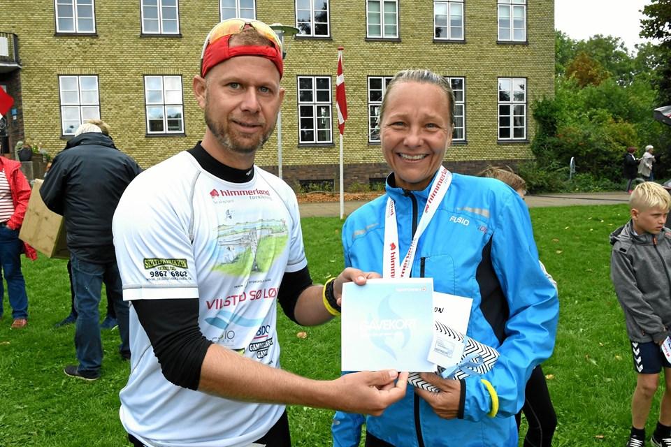 Løbsleder Rasmus Gammelholm Pedersen overrækker her gavekort til Heidi Jørgensen, Aalborg, for at sætte ny tidsrekord på halvmaratonruten. Privatfoto