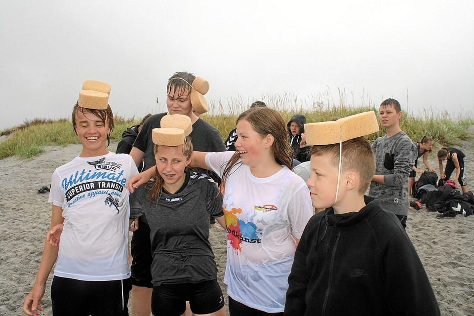 Med svampe på hovedet skulle eleverne hente vand i havet og fylde det i en spand.