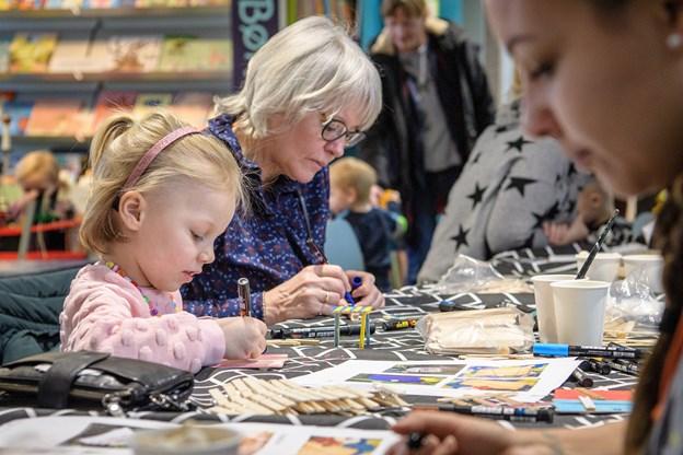 Cirkel Lundholm Danielsen fra Frederikshavn maler en dør ind til fehaven og mormor Gitte Kristiansen fra Skagen er i gang med et lille bord. Der er hyggestemning på tværs af generationer på biblioteket.