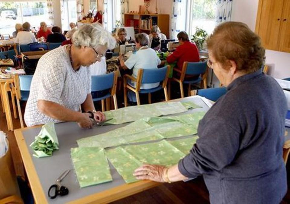Lilly Mose og Vera Fisker er i gang med at klippe stof til en kjole. Det er en ny model, der driller lidt. Forstykket bliver ikke samme størrelse som rygstykket. Foto: Peter Mørk.