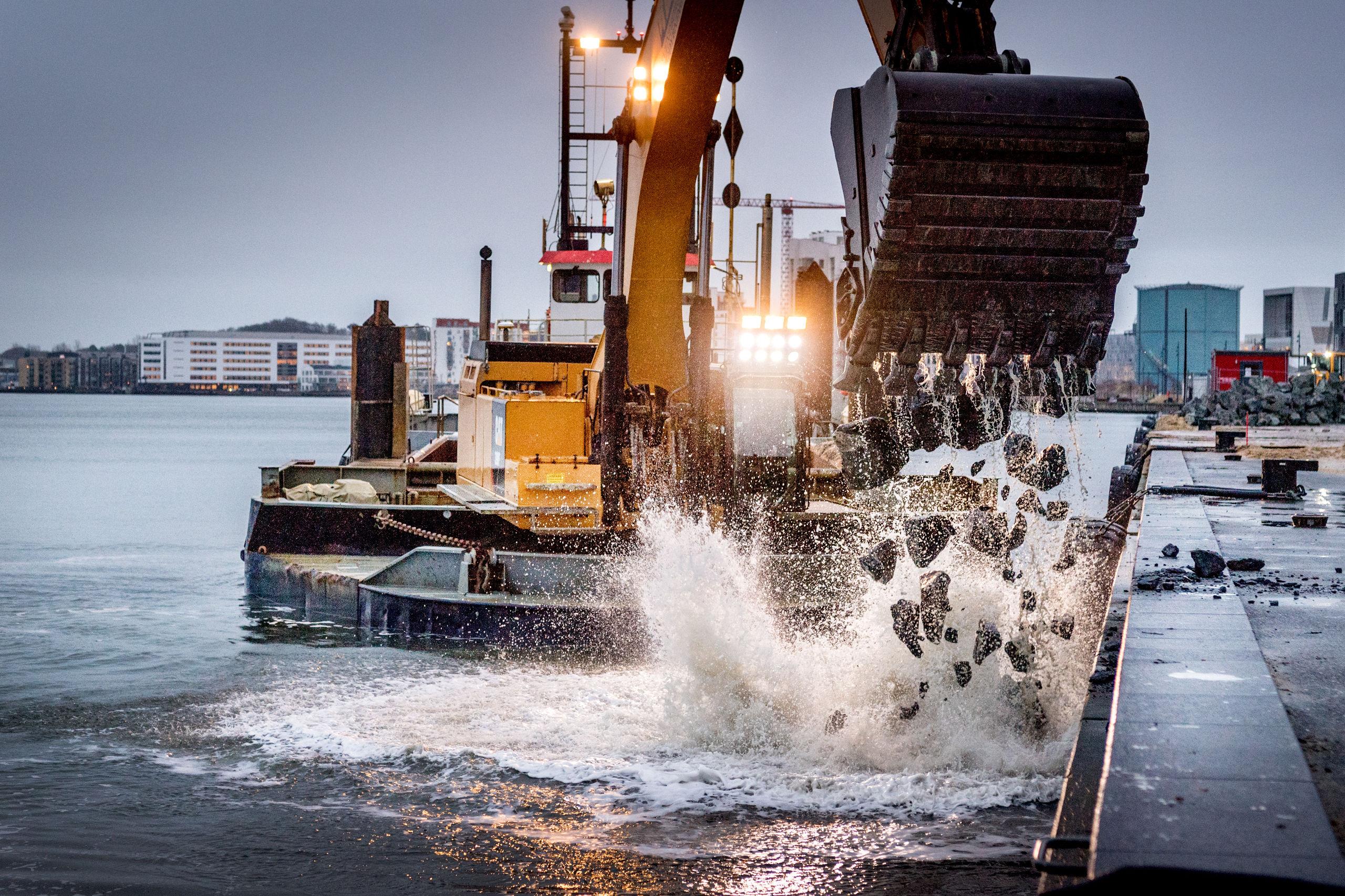 Det er et ganske imponerende syn, når den store og flydende gravko gnaver sig ind på de store mængder granitsten på kajen for derefter at hælde dem ud i Limfjorden. Foto: Torben Hansen
