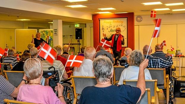 Beboerne havde fået flag og var med til at synge fødselsdagssangen for 90 års fødselaren. Foto: Mogens Lynge