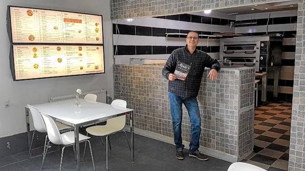 Alfredo viser stolt det store spisekort, både på væggen og i den trykte udgave. Foto: Karl Erik Hansen Karl Erik Hansen