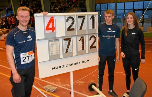 Kasper Larsen tv ved resultattavlen, som viser sit flotte resultat på 7,12 m i længdespring og ny Dansk Ung-seniormester. Klubkammeraterne Jeppe Bruun og Karoline Olesen. Privatfoto.