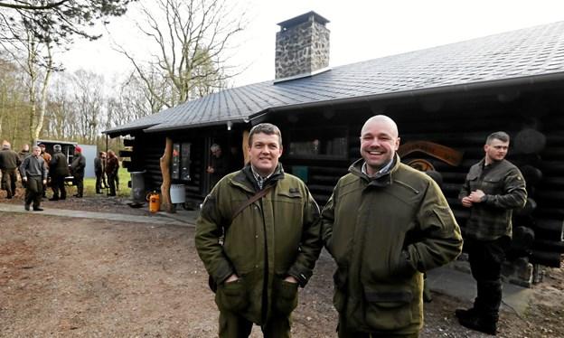 Finn Johansen og Morten Hede (t.h.) fra jagtforeningens bestyrelse foran hytten med det nyanlagte tag. Foto: Allan Mortensen