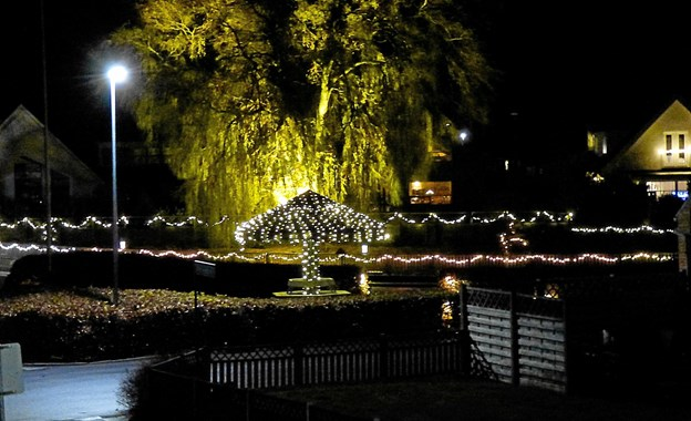 I lighed med tidligere år er der hundredvis af små lys omkring gadekæret, og paraplyen er klistret til med lys, ligesom der er lys på hængepilen i baggrunden. Foto: Ejlif Rasmussen Ejlif Rasmussen