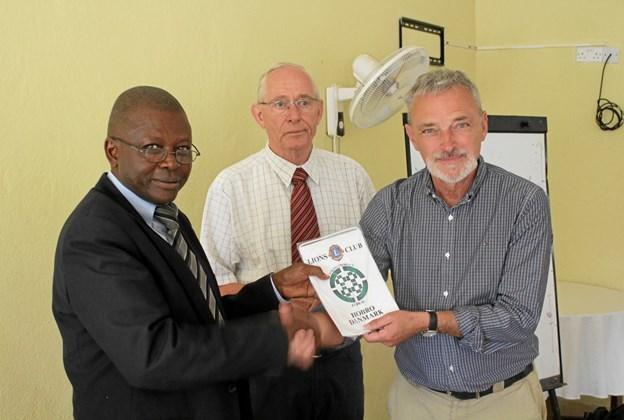 Jens Hald og Knud Trier overrækker Lions banner til Father Diido, formand for Rusccu.