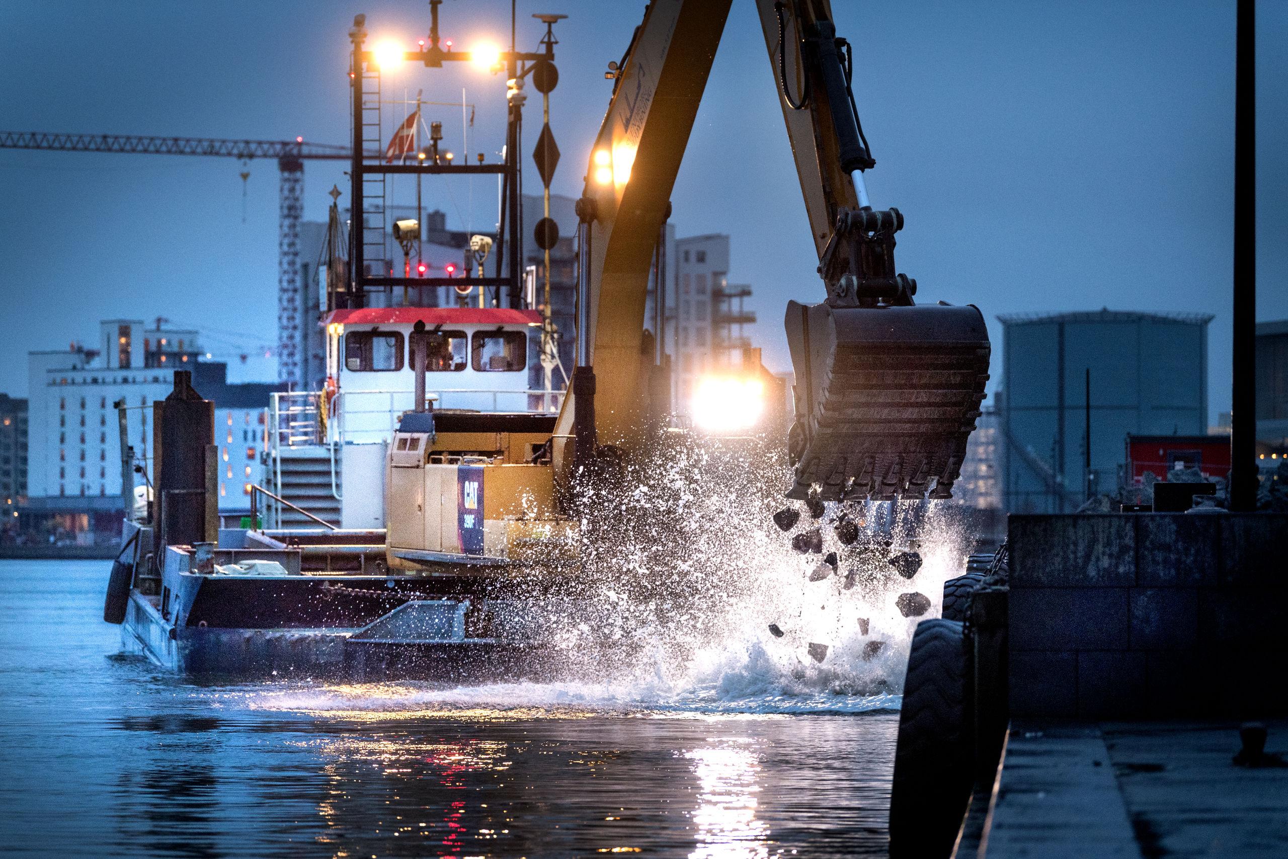De store huller på fjordbunden skal fyldes op og planeres ud, før man kan gå i gang med at støbe den enorme betonplade, der kommer til at rage ca. 13 meter ud fra selve kajen og som får en længde på ca. 185 meter. Foto: Torben Hansen
