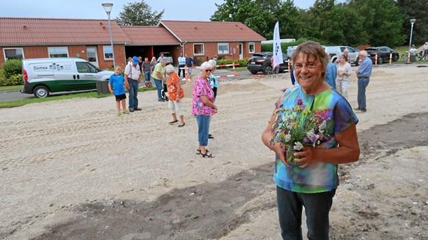 Naboerne på Skovbrynet mødte talstærkt op på byggepladsen, og Rita Rendow fra nr. 77 havde tilmed plukket en yndig markbuket til begivenheden. Foto: Ejgil Bodilsen