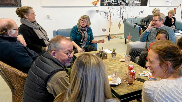 """Marianne Isager (for bordenden) og hendes mand Nels Gaardahl (i sofaen til højre) hyggede om gæsterne i """"Koserummet"""". Niels Helver"""