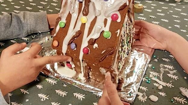 En af brunkagehusene i færdig stand. Børnene hjælper hinanden med at holde sammen på huset, mens glasuren sætter sig. Privatfoto