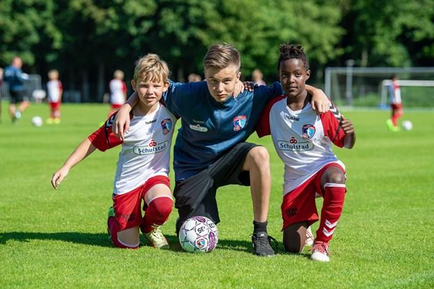 Hobro IK forsøger sig med ældre drenge og piger, der hjælpetræner yngre spillere - som her fra DBU's Fodboldskole i Hobro, hvor 15-årige trænerassistent William Elkjær, Hadsund, instruerer to 10-årige knægte fra Hobro - Søren (t.v.) og Domas. Foto: Henrik Bo