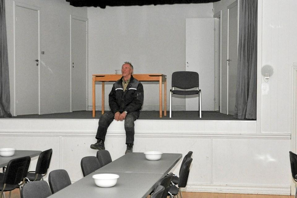 Heine Larsen er formand for bestyrelsen, og her sidder han på kanten af scenen og ser ud over salen, hvor der er gjort klar til en banko-aften, mens der fredag 8. februar er Irsk Aften.Foto: Ole Torp
