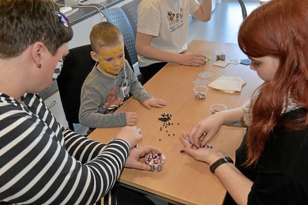 HAMA havde sponseret en masse perler. Her er Anja Thulsted (tv.), Nikolaj og Sabrine Tange i gang med at lave et dyr. Foto: Ole Iversen Ole Iversen