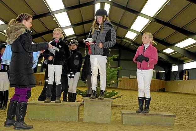 Amalie Andersen, Thea Lanng og Matilde Gregersen får medaljer for deres indsats i en af dressurklasserne. Privatfoto
