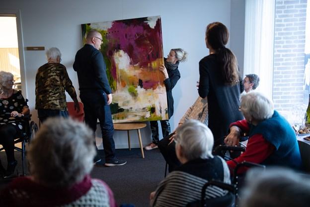 Peder Marlo fra Lux Vera og Janne Jacobsen hjalp hinanden med at pakke det nye maleri ud og fik det hængt op på væggen ved festsalen på Vivaldi. Foto: Hans Ravn