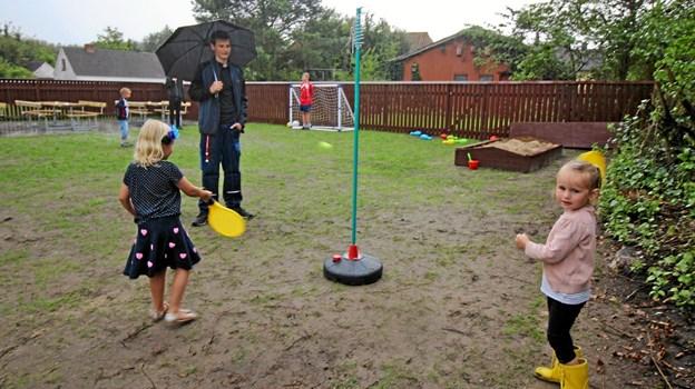 Det var vist mest til ære for fotografen, at børnene vovede sig ud på legepladsen. Regnen styrtede ned!  Foto: Jørgen Ingvardsen