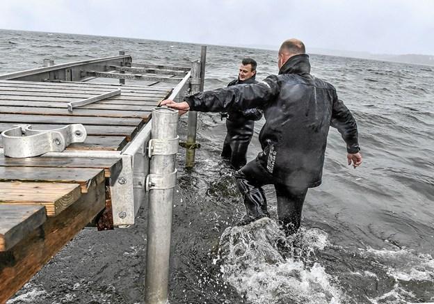 Tykke waders og vintertøj var i brug ved det kolde og våde arbejde at hente Søbadets badebro ind. Foto: Ole Iversen