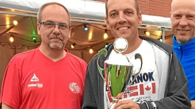 Formanden for SVIF, Mogens Juulsen overrækker HI's Henrik Kjeldsen pokalen for sejren ved sommerfodboldturneringen i Skallerup.