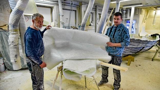 Glasfiber blev materialet i 1972, efter de første tre år med træ. Her holder Frank (bror til indehaver) og Danny Christensen en af glasfibermåtterne, som alle Limbo Både er bygget op af - i hånden.Foto: Ole Iversen Ole Iversen