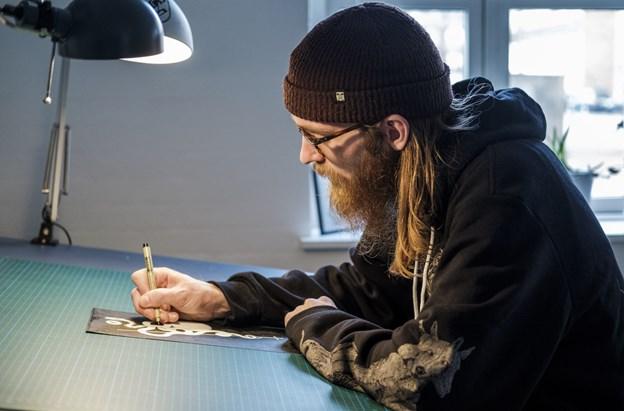 Ofte bliver han så grebet af arbejdet, at han sidder i flere timer og tegner. Men det ensformige arbejde er hårdt for hånden og øjnene. LASSE SAND Lasse Sand