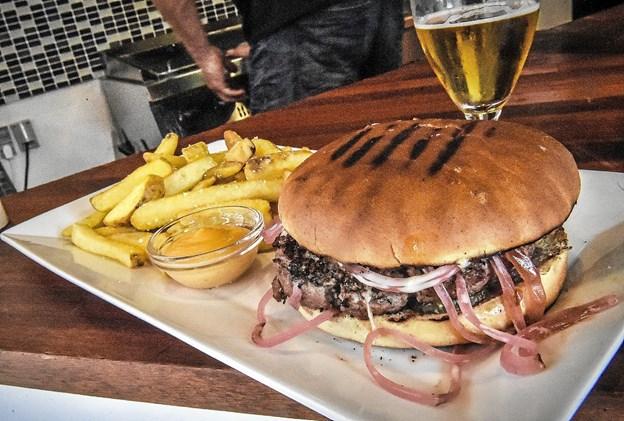 Hamburger med blandt andet ost, syltede rødløg og pickles, serveret med rustikke pommesfrites og en forrygende chili-mayo. Deres udsendte må sige - det var en god burger. Perfekt stegt, saftig og med fuld blus på smag. Ikke mindst mayoen, balanceretstærk, var en god makker til burgeren. Foto: Ole Iversen