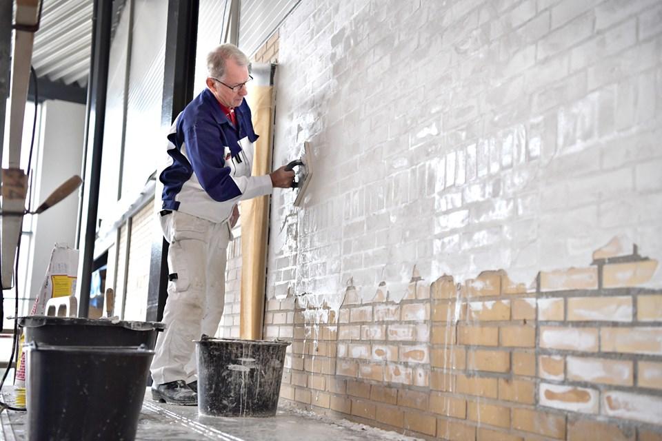 Erik Jespersen pudser væggen i centerets hjerte. Det er hårdt - men også hyggeligt - arbejde, og han får assistance fra Preben Larsen, der er tidligere arbejdskollega. Foto: Bente Poder