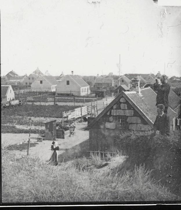 I 1892 kom den omvandrende stereoskopfotograf Peter Lorents Fangel til Skagen, hvor han lavede nogle bemærkelsesværdige optagelser. Her har han anbragt sig på den store klit bag det nuværende Thorkild Skarpæs gård, hvorfra man skuer mod øst. Der er luft mellem husene og plads til både hjeld og mindre kålgårde. Bagerst til venstre skimter man den nybyggede banegård. Foto: