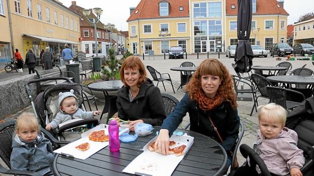 Søstrene Mai Brit og Jeanette Frydkjær sammen med børnene Malthe, Lærke og Olivia nyder 'løvfaldssommeren' og en lækker pizza på Sæby Torv. De har afsat to dage til at komme rundt i byen og til at besøge andre aktiviteter. Foto: Tommy Thomsen