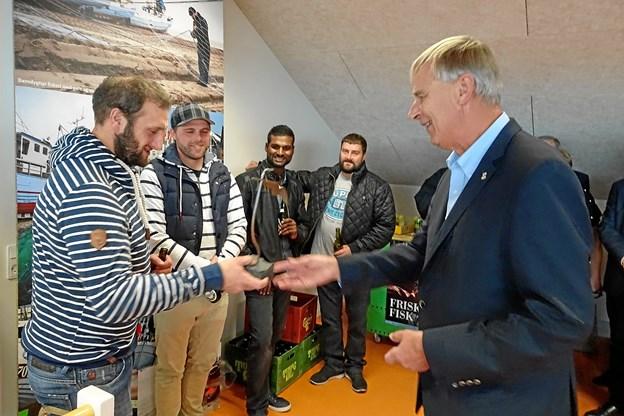 Rotary-præsident Peter Eigenbroth overrækker en statuette af en fugl til kystfiskerlaugets formand, Jan Olsen.Privatfoto