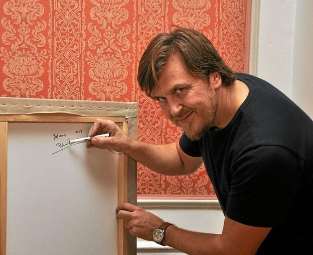 Kunstneren Peter Basse er mester for to dejlige billeder i Dronningesalen, og da slottet har købt netop disse billeder, var han til stede og signerede dem på bagsiden.Foto: Ole Torp Ole Torp