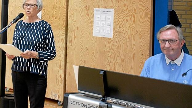 Formanden for Ældrerådet i Hjørring Kommune Lene Smidstrup holder åbningstalen, og Henrik Klitgaard spiller hyggemusik under det store Spis Sammen arrangement. Foto: Niels Helver
