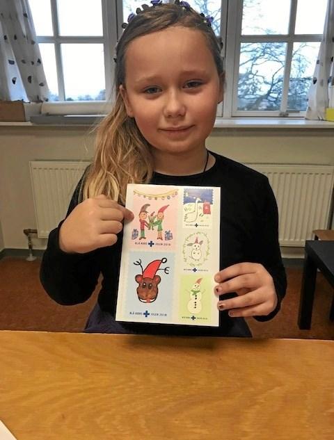 Melissa er stolt over sin tegning, der viser en far og en mor og en glad baby. Foto Jesper Larsen