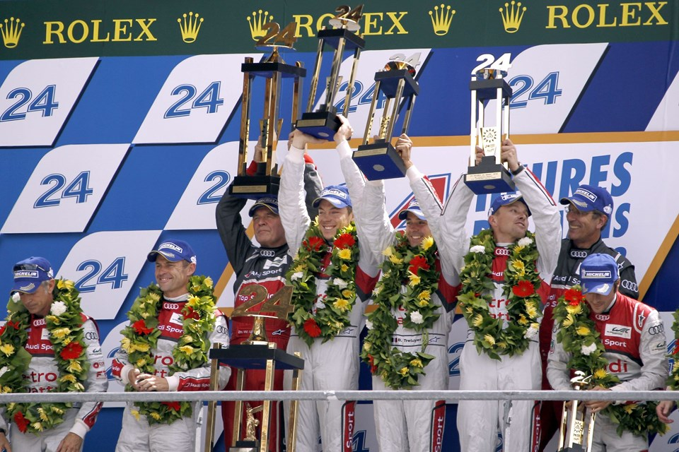 (C,LtoR) Drivers of the Audi R18 E-Tron Quattro Nº1, German Andre Lotterer, French Benoit Treluyer, Swiss Marcel Faessler, celebrate on the podium and raise their trophies with Audi's team manager Wolfgang Ulrich (C,L), after winning the 80th edition of Le Mans 24 hours endurance race, on June 17, 2012 in Le Mans, western France. Audi have now won 11 of the last 13 races at Le Mans since 1999, while for the trio of Treluyer, Fassler and Lotterer it was a second win in succession. It was the first time that a hybrid car had won the prestigious race since its inception in 1923. AFP PHOTO / CHARLY TRIBALLEAU