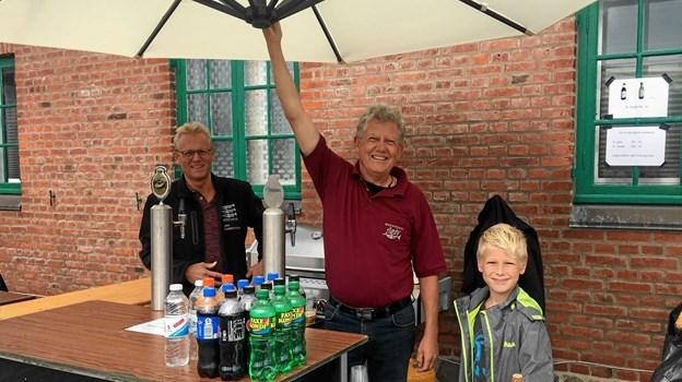 Både blæst og regn prægede dagen, så Mogens Aarup var fast parasolholder, så Jan Halbak Christensen (tv)og Johan Vive Aarup (th) kunne sælge øl, vand, kaffe og kage i tørvejr.