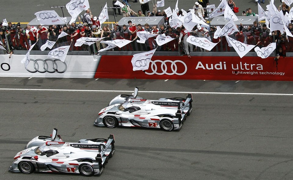 Audi team mechanics celebrate in the stands after Andre Lotterer of Germany driving the Audi R18 E-Tron Quattro Number 1 crossed the finish line to win the Le Mans 24-hour sportscar race in Le Mans, central France June 17, 2012. The Audi Number 1 was also driven by Benoit Treluyer of France, and Marcel Fassler of Switzerland. REUTERS/Regis Duvignau (FRANCE - Tags: SPORT MOTORSPORT)